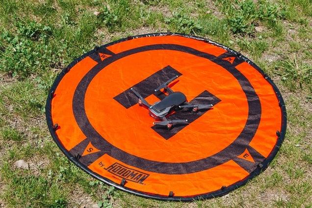 Una plataforma de lanzamiento de drones redonda y naranja con marcas negras. Un dron está sentado en el centro.