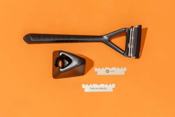 Los componentes del kit de inicio Leaf, incluida la maquinilla de afeitar y el paquete de 10 hojas, dispuestos cuidadosamente junto con el soporte