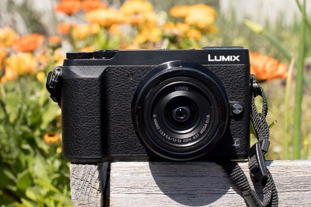 Una cámara sin espejo Panasonic Lumix DMC-GX85 negra colocada sobre un trozo de madera con flores visibles en el fondo.